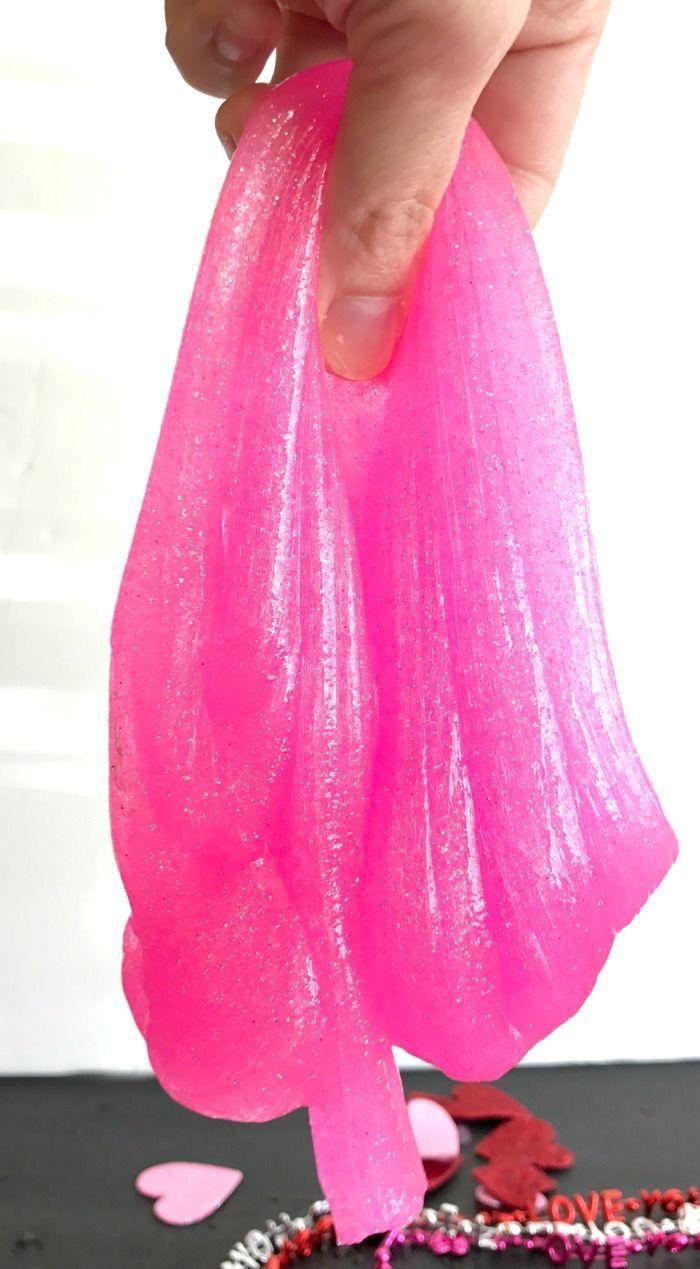 Ingredienti slime di colore rosa e molto elastico, pasta modellabile tenuta sospesa in mano