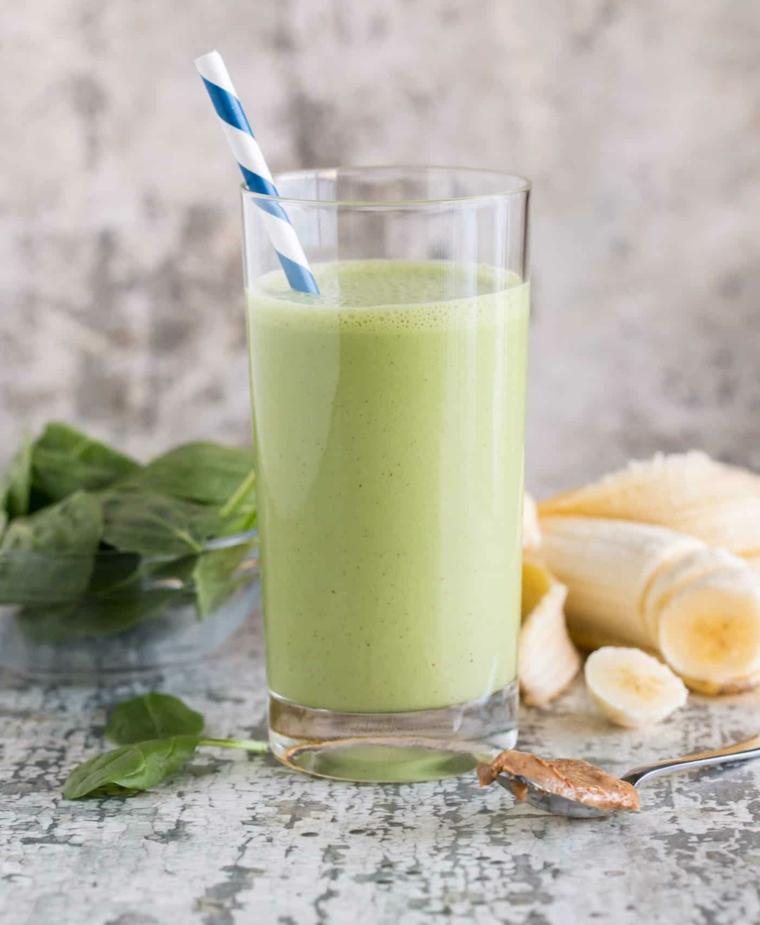 Frullato a base di banana e spinaci, smoothie allungato con acqua e servito in un bicchiere alto