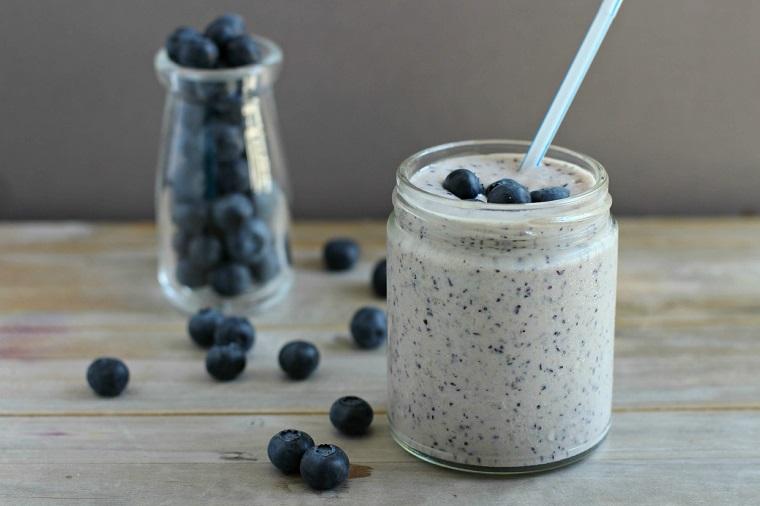 Barattolo di vetro con smoothie ai mirtilli e gelato alla vaniglia, tavolo di legno con bottiglietta e frutta sparsa