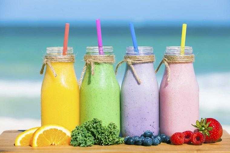 Frullati di frutta in bottiglie di vetro e cannucce colorate, frutta su un tagliere di legno