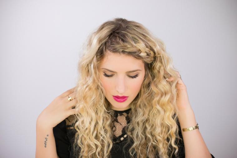 ragazza con un tatuaggio sul polso, anelli e bracciali dorati, come farsi i capelli mossi