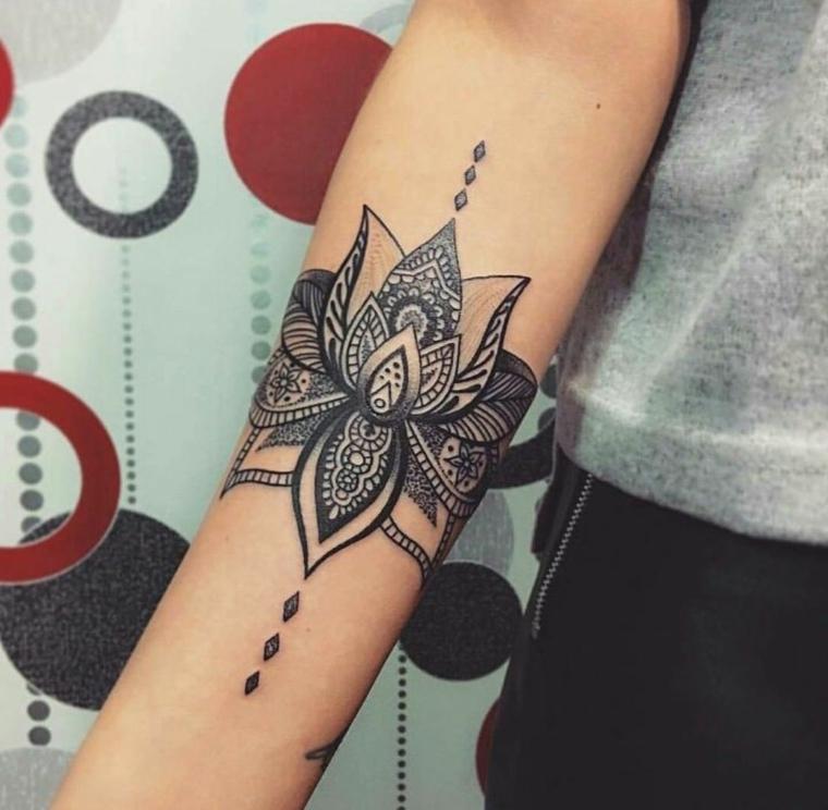 Fiore di loto tattoo significato sull'avambraccio di una donna con ornamenti e forme geometriche