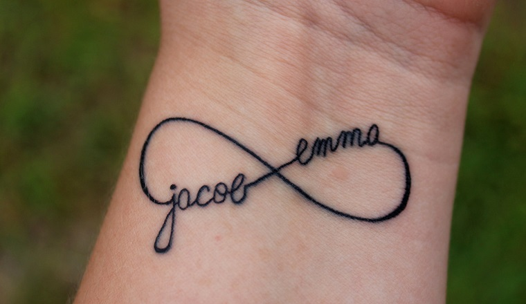Tatuaggio dedicato alla famiglia con il simbolo dell'infinito e i nomi dei figli
