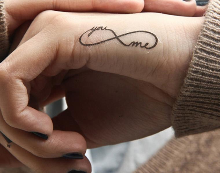 Tattoo famiglia e un'idea con il simbolo dell'infinito tatuato sulla mano di una donna