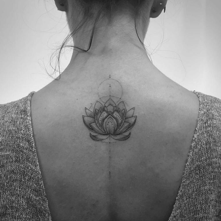 Fiore di loto tattoo sulla schiena di una donna con forme geometriche e puntini