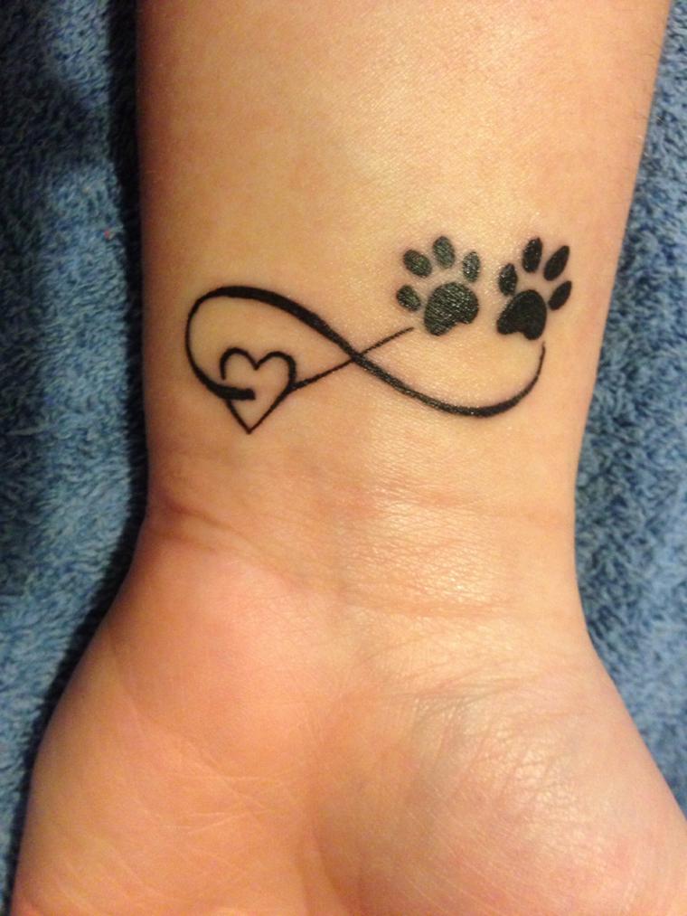 Tattoo famiglia con il simbolo dell'infinito e due impronte di cane sul polso