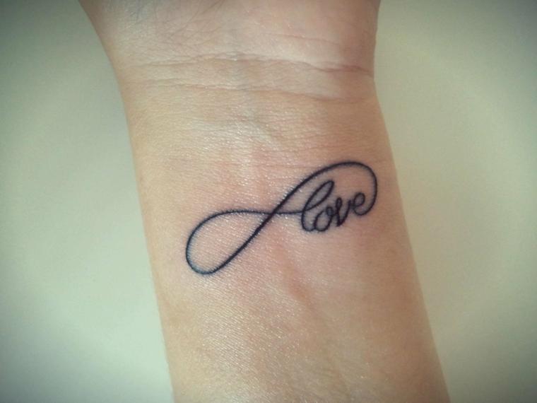 Tatuaggi con scritte e il segno dell'infinito, tattoo sul polso della mano di una donna