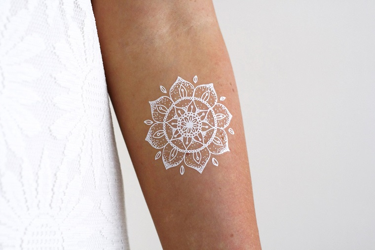 Mandala significato e un piccolo tatuaggio sul braccio di una donna con inchiostro di colore bianco