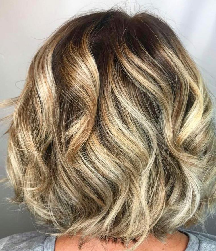 colore di capelli di tendenza, balayage capelli biondi ondulati con un taglio corto
