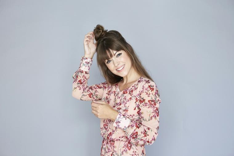 ragazza sorridente con un vestito dalla fantasia floreale e uno chignon, come fare capelli ondulati