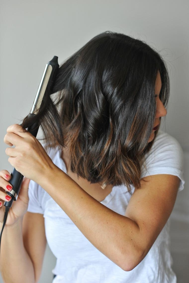 ferro arricciacapelli per realizzate una piega capelli mossi, ragazza castana con smalto rosso