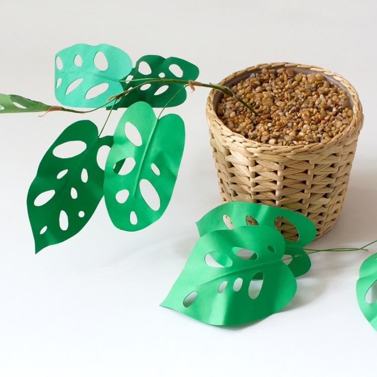 Lavoretti di carta, cesto di vimini con ghiaia decorativa e una pianta finta con foglie verdi