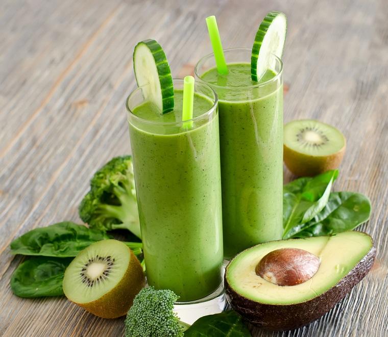 Due bicchieri con smoothie verde alla frutta e verdura, ingredienti posizionati su un tavolo di legno