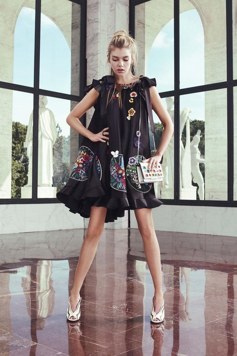 Donna con un vestito fluido con patch in abbinamento con la borsa tracolla e le scarpe