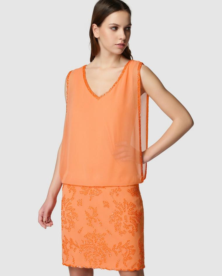 Donna con un vestito di colore arancione, top trasparente e parte inferiore con pizzo