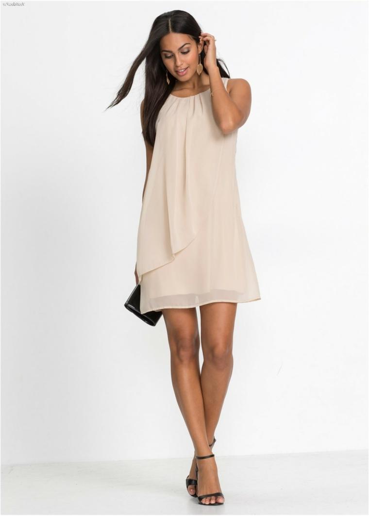 Donna con un vestito di colore beige corto e fluido, abbinamento scarpe e borsetta