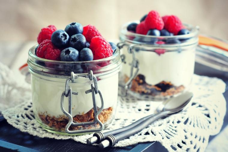 Barattoli di vetro con yogurt greco e biscotti, decorazione con frutti di bosco come mirtilli e lamponi
