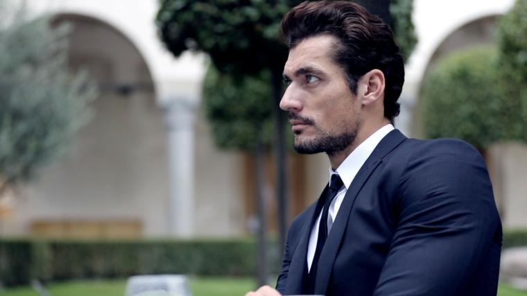 Uomo con capelli leggermente lunghi e pizzetto corto, vestito in modo elegante con giacca e cravatta