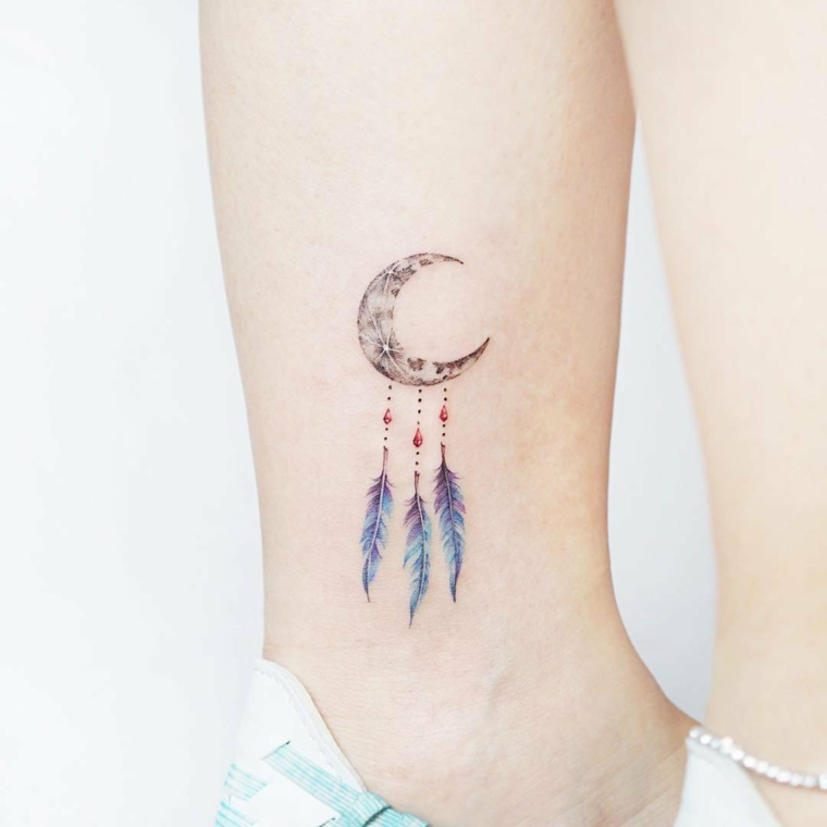Tatuaggi alla caviglia femminili, disegno tattoo con un acchiappasogni con piume colorate