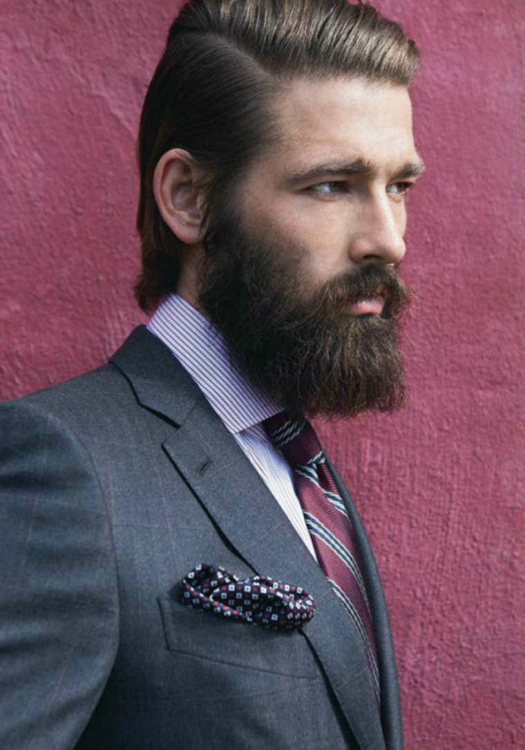 Barba incolta di un ragazzo vestito elegante con capelli rasati di lato e ciuffo tirato indietro