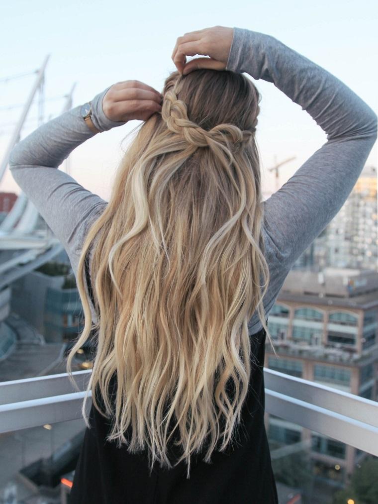 Treccia a cascata per dei capelli biondi e lunghi di una ragazza con maglione grigio