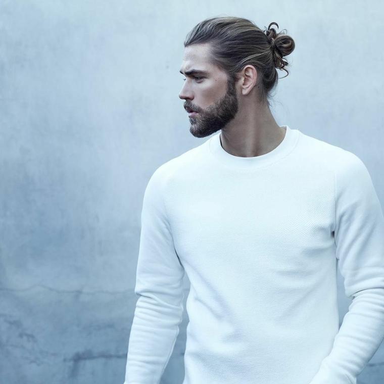 Come curare la barba, uomo con capelli biondi legati a chignon e vestito con maglia bianca