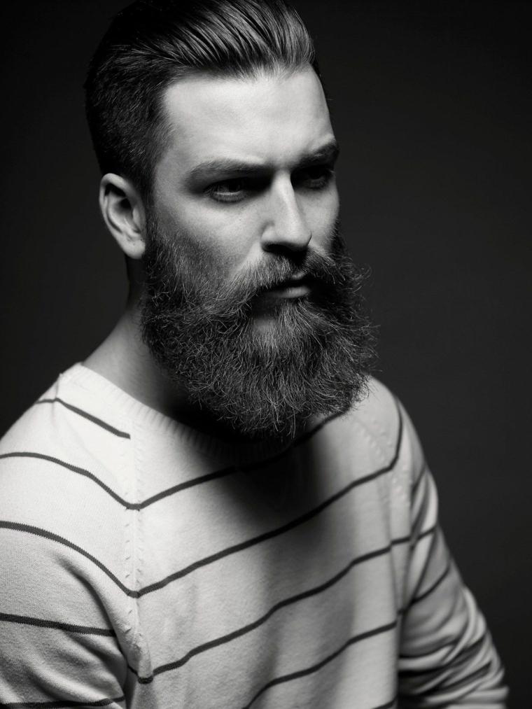 Un uomo con la barba lunga e baffi, foto bianco e nera con sfondo scuro