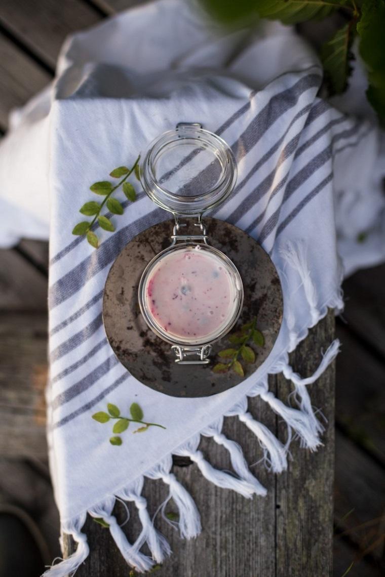 Come fare lo scrub a base di mirtilli e yogurt, barattolo di vetro su una tovaglia e panchina di legno