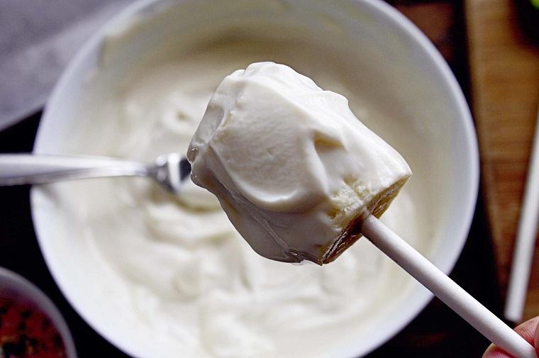 Immergere il bastoncino la banana nello yogurt, idea per dei dolci semplici e veloci