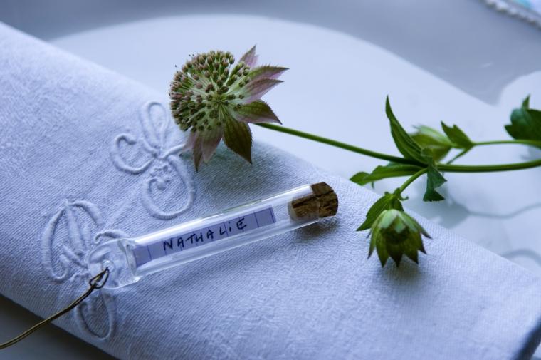 Segnaposto matrimonio con una bottiglietta di vetro con all'interno il nome dell'invitato
