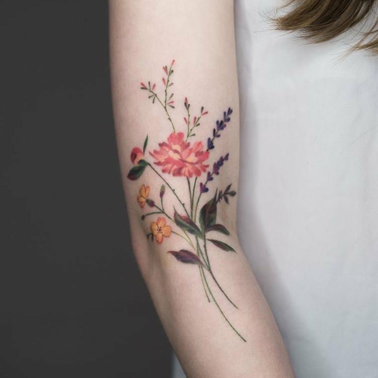 Tatuaggio braccio donna con un disegno colorato di fiori come lavanda