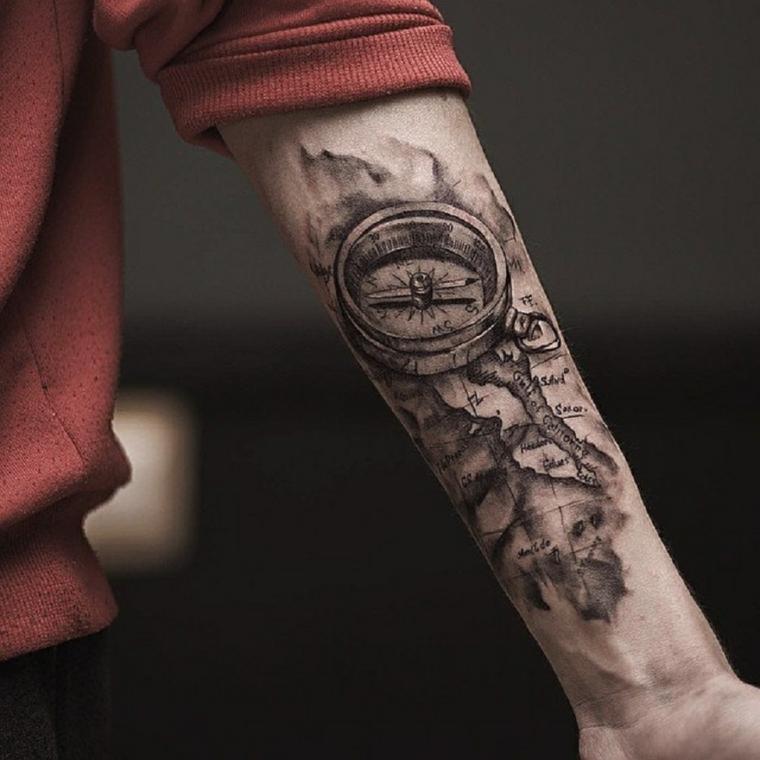 Tatuaggio sul braccio sinistro di un uomo con una bussola e scritte su una mappa