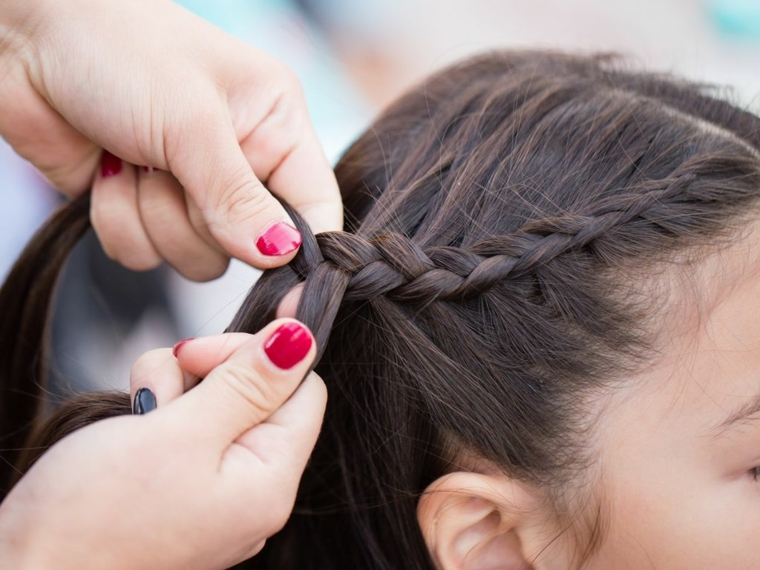 Trecce attaccate alla testa di un lato per dei capelli lisci di colore castano