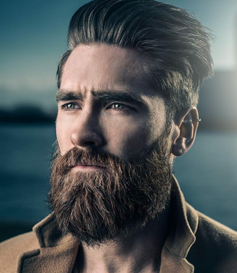 La barba incolta di un uomo con capelli lunghi e acconciatura rasati di lato