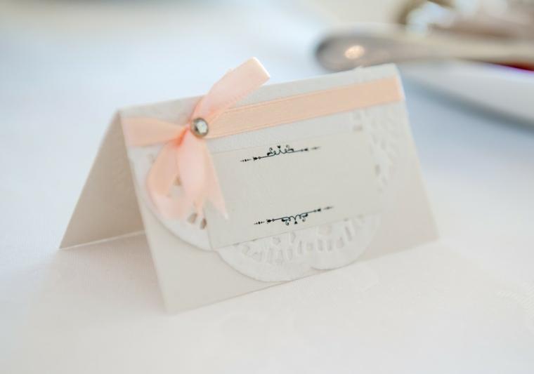 Elegante cartolina bianca e fiocco rosa, segnaposto fai da te per un matrimonio