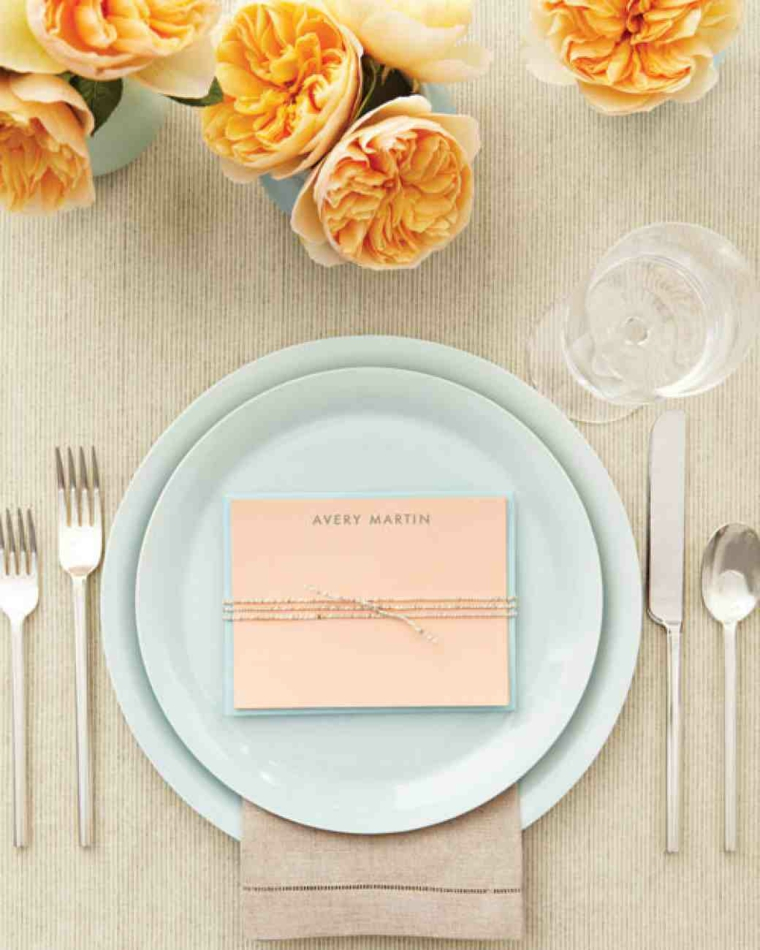 Segnaposto matrimonio con una cartolina di colore rosa su un tavolo decorato con fiori