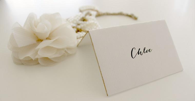 Segnaposto matrimonio con una cartolina con il nome scritto dell'invitato