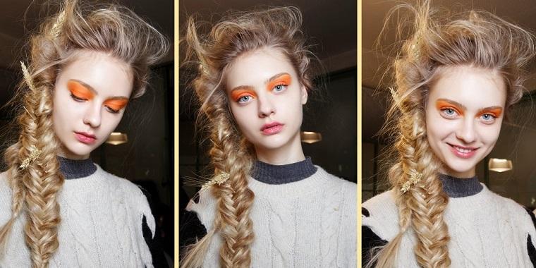 Treccia a spina di pesce per dei capelli lunghi di colore biondo, ragazza truccata con ombretto arancione