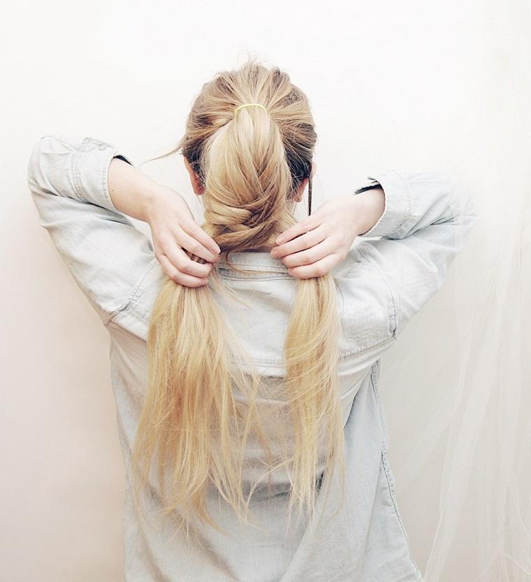 Treccia a spiga su dei capelli legati con elastico di colore biondo, ragazza che si fa un'acconciatura