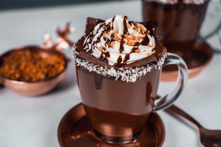 Dolci veloci senza cottura, tazza di vetro con cioccolata calda, decorazione bevanda con panna