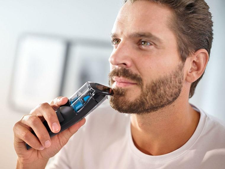Uomo che si sta regolando la barba con rasoio elettrico, prodotti per far crescere la barba