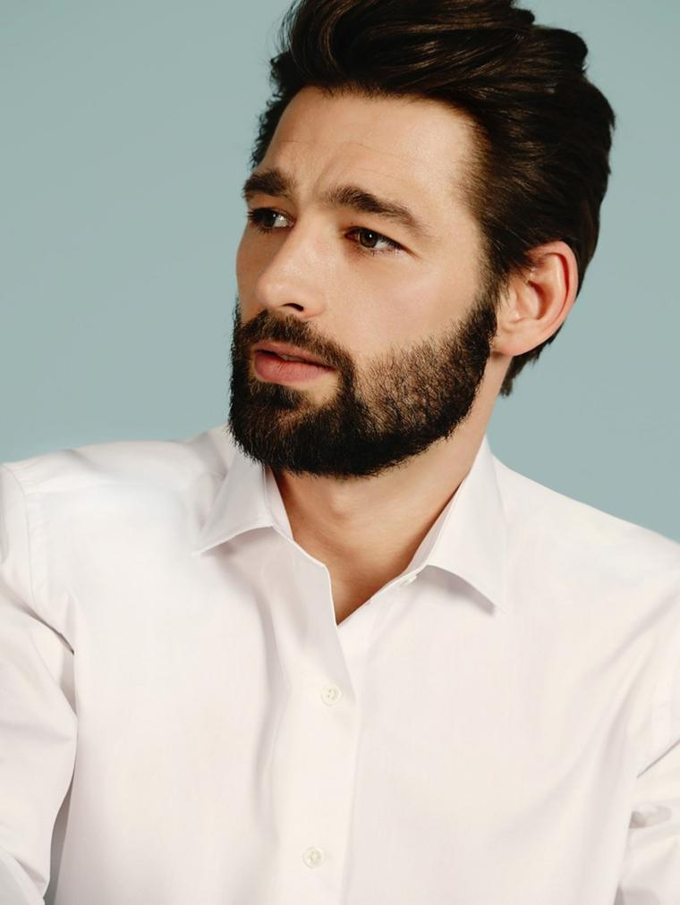 Uomo con capelli castani scompigliati e una barba corta e folta