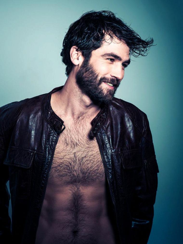 La barba incolta di un uomo, ragazzo con capelli neri leggermente più lunghi davanti
