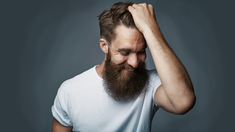 Uomo con mano fra i capelli, viso sorridente con una barba lunga e folta