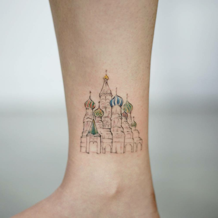 Tattoo caviglia con disegno colorato di un castello, gamba di un uomo con tatuaggio