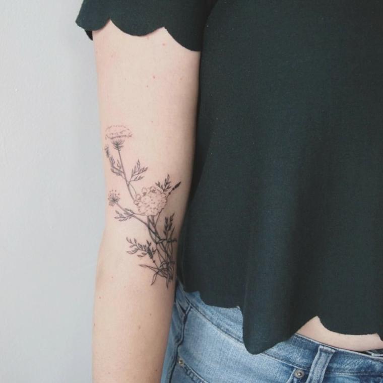 Idea tatuaggi avambraccio di una donna con dei fiori colorati, abbigliamento casual con maglietta e jeans