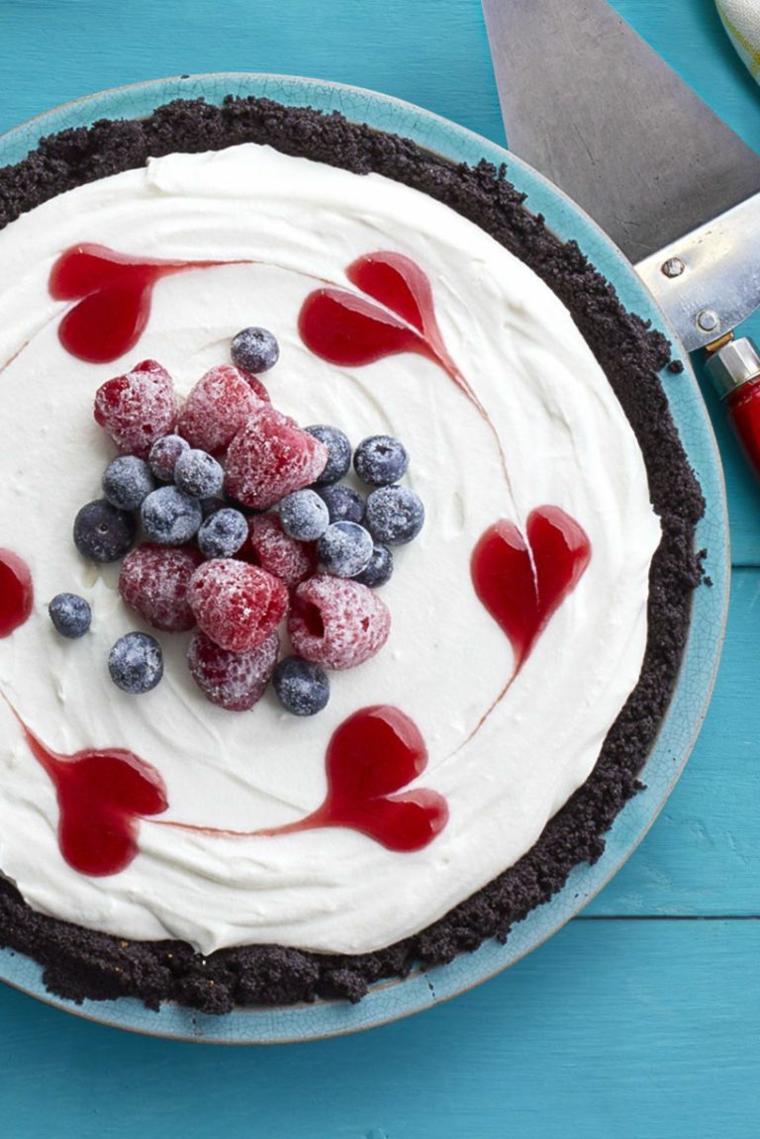 Torte fredde e un'idea con uno strato di biscotti sbriciolati e panna montata, decorazione con frutti di bosco congelati
