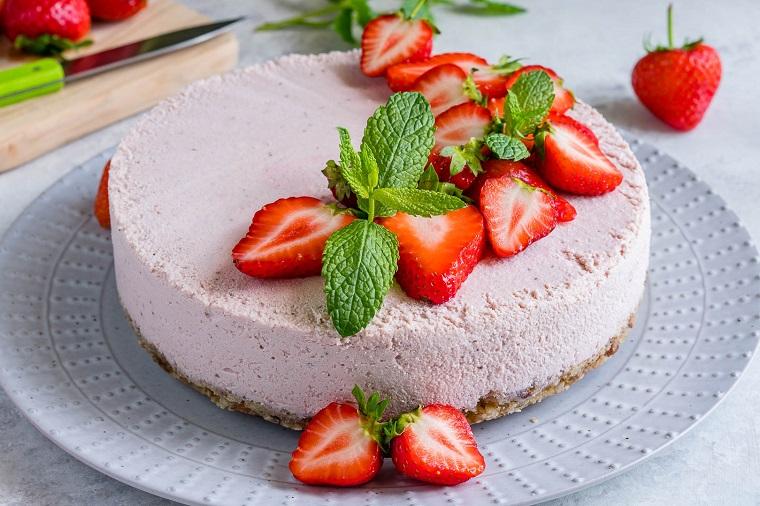 Torte fredde e una cheesecake con fragole e foglie di menta come decorazione