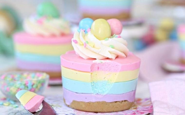 Dolce con biscotti secchi e diversi strati colorati di cheesecake con panna montata in cima