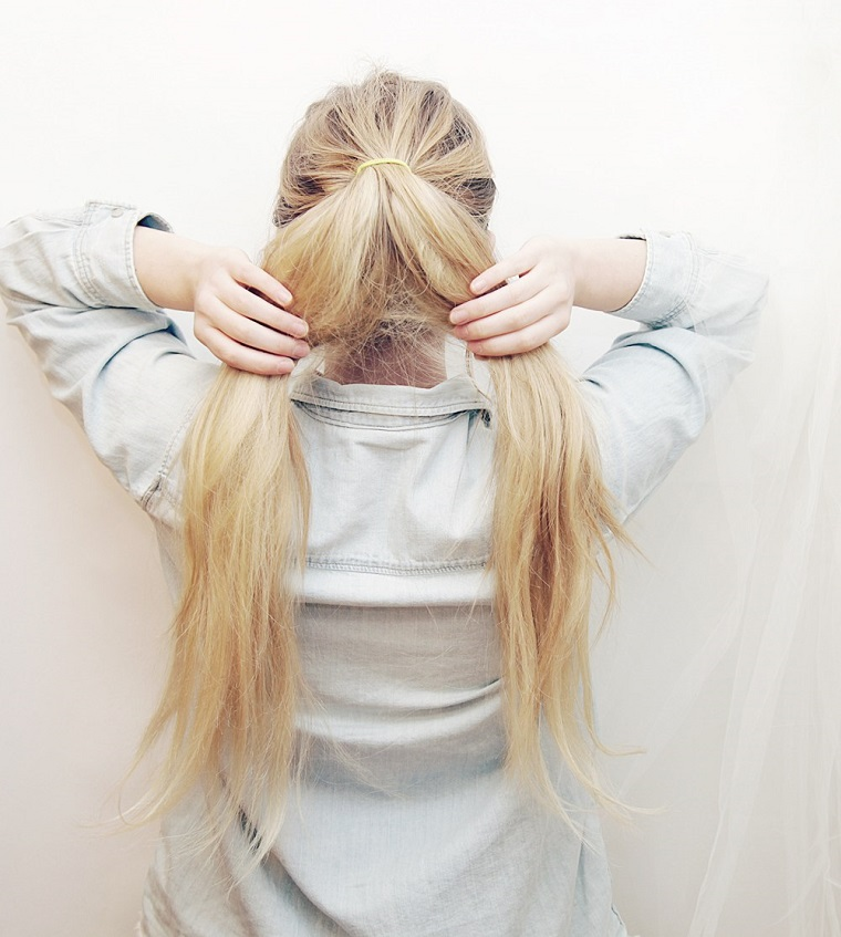 Tutorial trecce alla francese, donna con i capelli biondi legati e divisi in due sezioni
